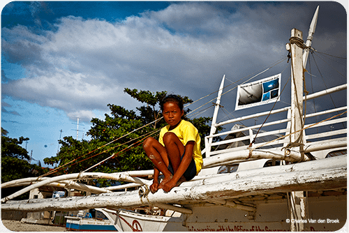 A local girl taking time to relax on a traditional Filipino bangka boat